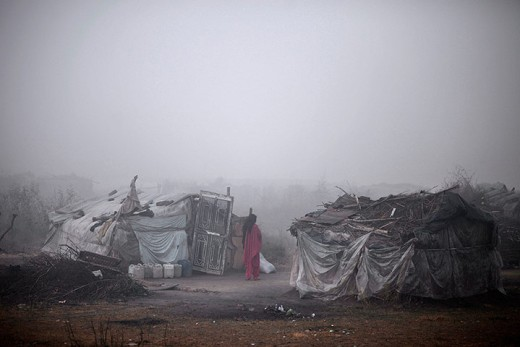 A woman stands outside her makeshift home in Islamabad
